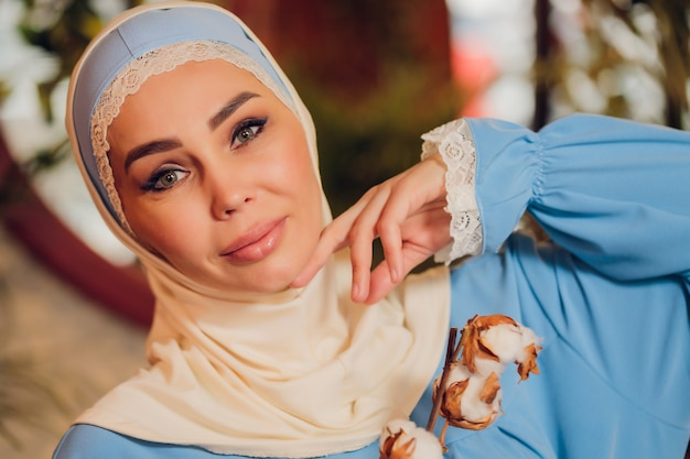 Young beautiful caucasian woman wearing traditional muslim headscarf in hipster coffee shop with big full length windows. female in blue hijab at cozy cafe. background, copy space, close up portrait.