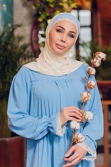 큰 전체 길이 창문이 힙 스터 커피 숍에서 전통적인 이슬람 headscarf를 입고 젊은 아름 다운 백인 여자. 아늑한 카페에서 파란색 hijab의 여성. 배경, 복사 공간, 초상화를 닫습니다.