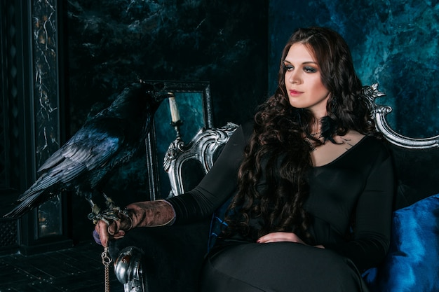 Young beautiful caucasian woman with black raven on her hand sitting on sofa