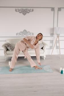 Giovane bella donna caucasica con capelli biondi e bel viso che fa yoga in pose diverse a