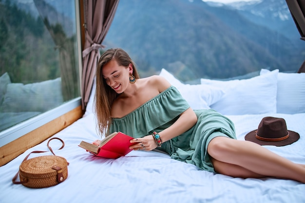 Young beautiful charming happy cute smiling woman passionate about reading exciting book while lying on bed with mountain view