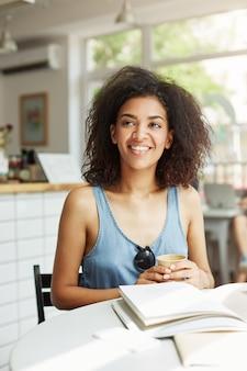 Seduta di risata sorridente della giovane bella studentessa africana allegra in caffè. riviste di libri sdraiato sul tavolo. apprendimento ed educazione.