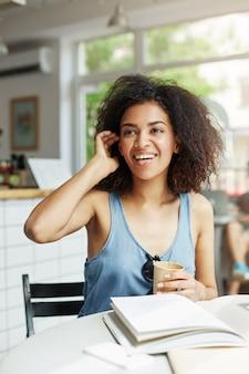 Сидеть молодого красивого жизнерадостного африканского студента женщины усмехаясь смеясь над в кафе. книги журналов лежат на столе. обучение и воспитание.