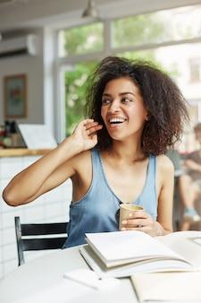 カフェに座って笑って笑っている若い美しい陽気なアフリカ女性学生。テーブルの上に横たわる本の雑誌。学習と教育。