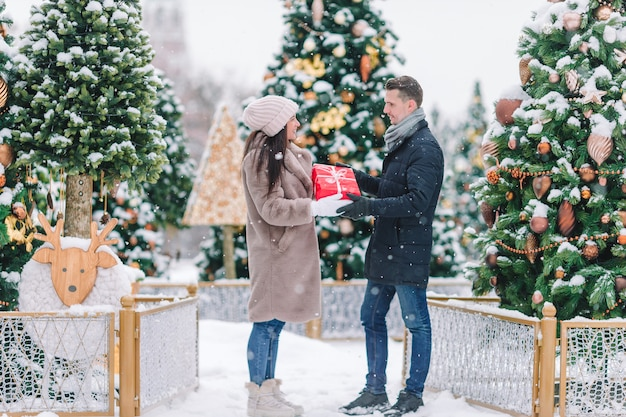 Young beautiful cheerful couple celebrating christmas in the city street and giving gift to each other.