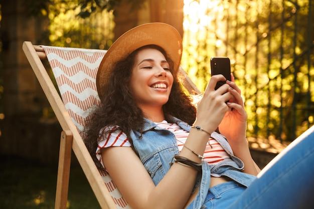 携帯電話でおしゃべりする若い美しい陽気な巻き毛の女性。