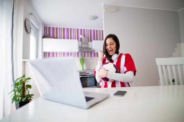 Young beautiful cheerful girl in red and white jersey is watching a soccer match cheering on her laptop being happy with the score while holding a ball.