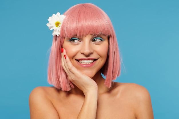 Giovane bella signora dai capelli rosa allegra con trucco colorato tenendo la mano sulla guancia mentre guarda da parte con un ampio sorriso felice, in piedi