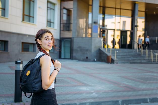 若い美しい陽気な学生はしかめっ面し、大学に行く途中で楽しんでいます