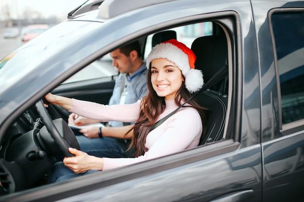 Молодая красивая жизнерадостная женщина сидит на месте водителя в машине.
