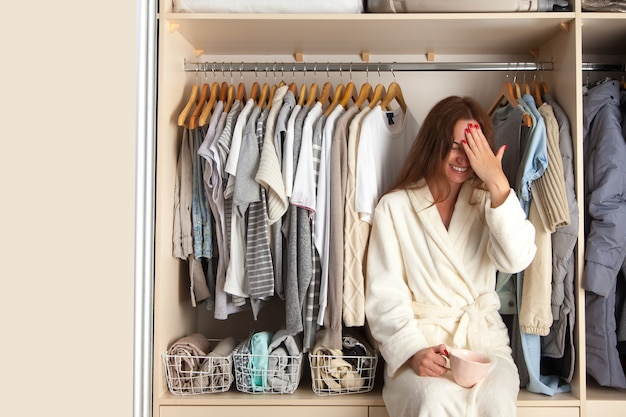 Young beautiful cheerful woman sits in a closet with a mug. organization of the wardrobe. clothes storage.