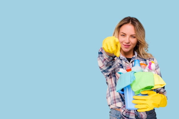 Young beautiful cleaner woman holding bucket with products pointing at camera against blue backdrop