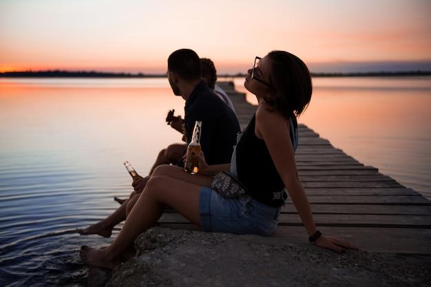 Молодая красивая компания друзей отдыхает на берегу моря во время восхода солнца