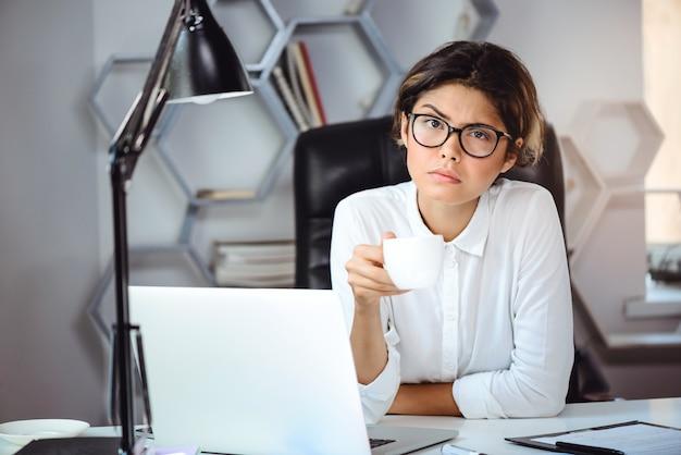 Caffè bevente della giovane bella donna di affari sicura nel luogo di lavoro in ufficio.