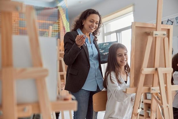 Молодая красивая уверенная в себе учительница помогает ребенку рисовать на групповом уроке в белом современном минималистичном классе