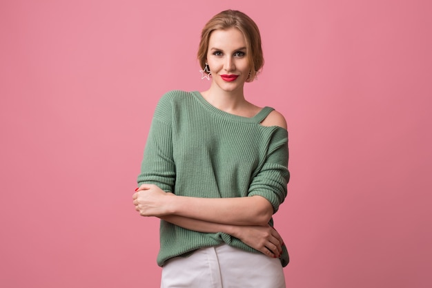 若い美しい自信を持って女性、赤い唇、セクシーな表情、緑のカジュアルセーター、組んだ腕、スタイリッシュなスタジオでポーズをとるモデル、分離、ピンクの背景、カメラで見て