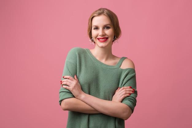 若い美しい自信を持って女性、赤い唇、笑顔、幸せ、緑のカジュアルセーター、組んだ腕、スタイリッシュなスタジオでポーズをとるモデル、分離、ピンクの背景、カメラで見て