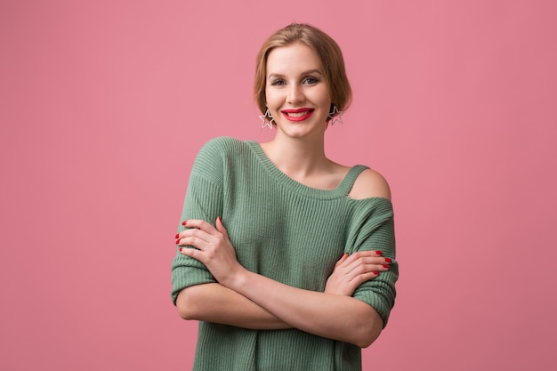 Young beautiful confident woman, red lips, smiling, happy, green casual sweater, crossed arms, stylish, model posing in studio, isolated, pink background, looking in camera