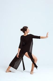 Молодой красивый современный танцор представляя над белой стеной. копировать пространство