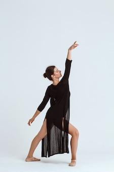 Giovane bello ballerino contemporaneo che posa sopra la parete bianca. copia spazio.