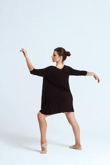 Giovane bello ballerino contemporaneo che posa sopra la parete bianca