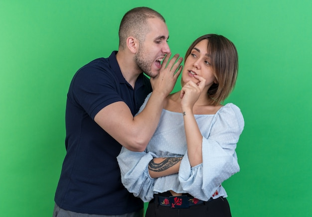 Молодая красивая пара сердитый человек кричит на ухо своей неосторожной подруге стоя