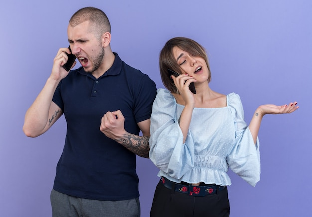 Young beautiful couple angry man shouting while talking on mobile phone while his happy girlfriend smiling talking on mobile phone standing over blue wall