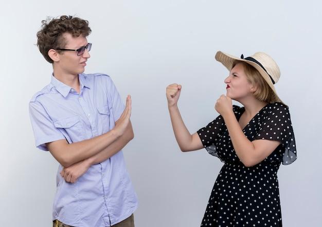 Молодая красивая пара злая женщина смотрит со сжатыми кулаками на своего смущенного парня, который показывает жест стоп над белой стеной