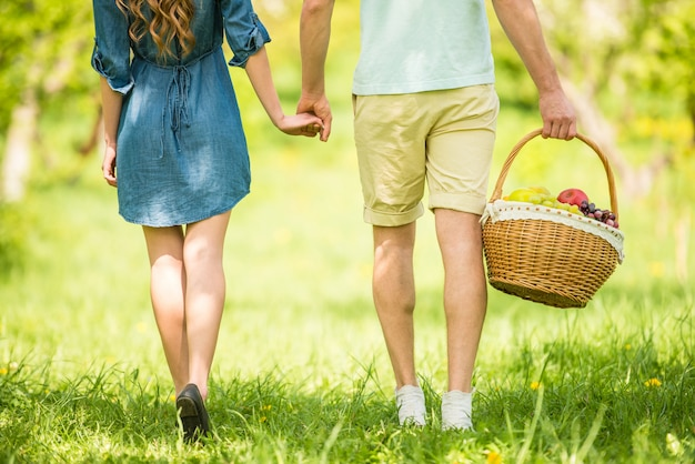 Young beautiful couple are going to picnic in summer park.