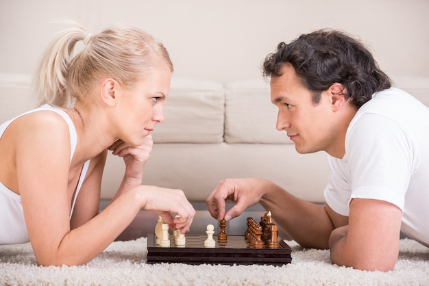 Young beautiful couple are playing chess at home.