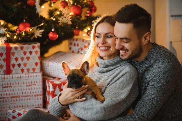 아름 다운 젊은 부부는 크리스마스 직전에 축제 새해 거실에서 강아지와 함께 놀고 있습니다