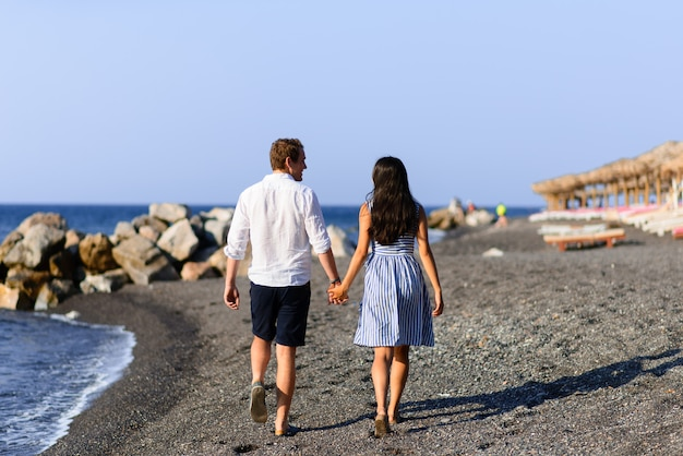 Young beautiful couple are walking on the background of the sea. shot on santorini beach.