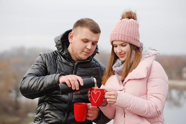 겨울에 피크닉에서 젊은 아름 다운 부부 그들은 커피를 마시는