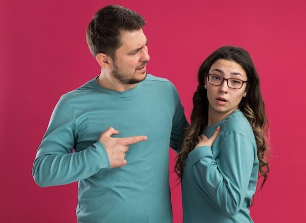 Giovane bella coppia in abiti casual blu confuso uomo che punta con indice figner alla sua ragazza sorpresa in piedi sul muro rosa