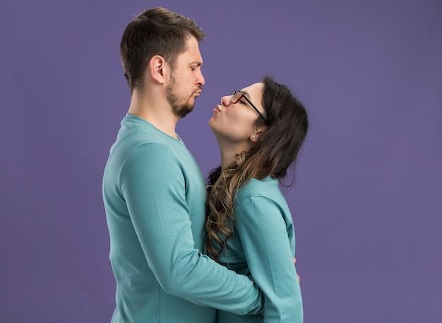 Giovane bella coppia in abiti casual blu uomo e donna felici e allegri che si abbracciano andando a baciarsi felici innamorati festeggiando san valentino