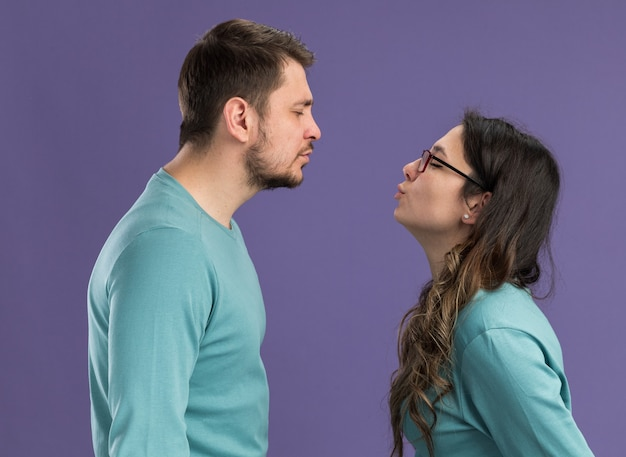 Young beautiful couple in blue casual clothes happy and cheerful man and woman going to kiss happy in love standing over purple wall