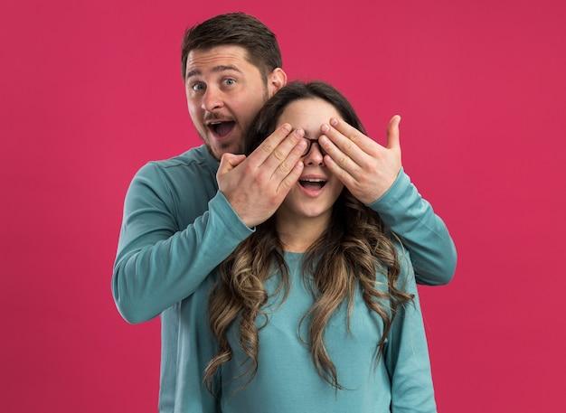 Giovane bella coppia in abiti casual blu uomo che chiude gli occhi della sua ragazza facendo una sorpresa felice innamorata insieme in piedi sul muro rosa