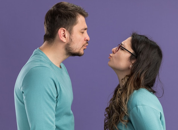 Young beautiful couple in blue casual clothes man and woman going to kiss happy in love standing over purple wall