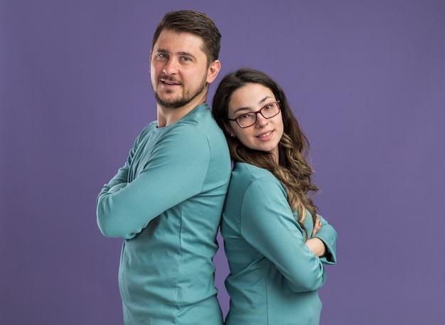 Giovane bella coppia in abiti casual blu uomo e donna felici innamorati in piedi schiena contro schiena sul muro viola