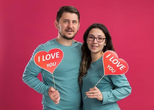 Giovane bella coppia in abiti casual blu uomo e donna che tengono cuori su bastoncini sorridenti allegramente felici innamorati insieme celebrando i giorni di san valentino in piedi sul muro rosa