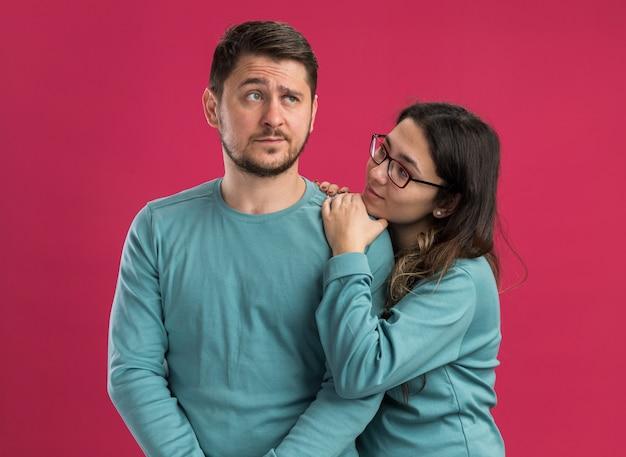 Giovane bella coppia in abiti casual blu donna che guarda con amore il suo ragazzo confuso in piedi sul muro rosa