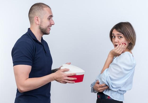 Giovane bella coppia in abiti casual uomo felice che fa un regalo alla sua ragazza stupita e sorpresa in piedi sul muro bianco
