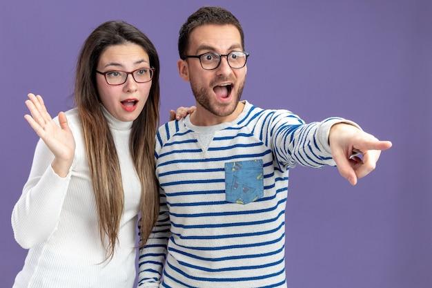 Giovane bella coppia in abiti casual felice e sorpreso uomo e donna che osserva da parte per celebrare san valentino in piedi sul muro viola