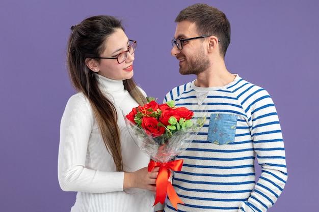Giovane bella coppia in abiti casual donna felice con bouquet di rose rosse guardando il suo ragazzo sorridente che celebra il giorno di san valentino in piedi sul muro viola