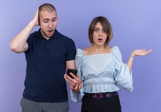 Giovane bella coppia in abiti casual uomo con smartphone e donna che sembra confusa allargando le braccia ai lati in piedi