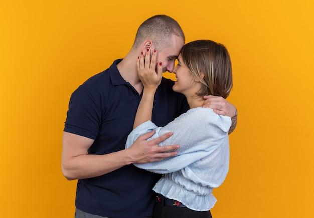 Giovane bella coppia in abiti casual uomo e donna che si abbracciano felici innamorati sorridendo allegramente in piedi sul muro arancione