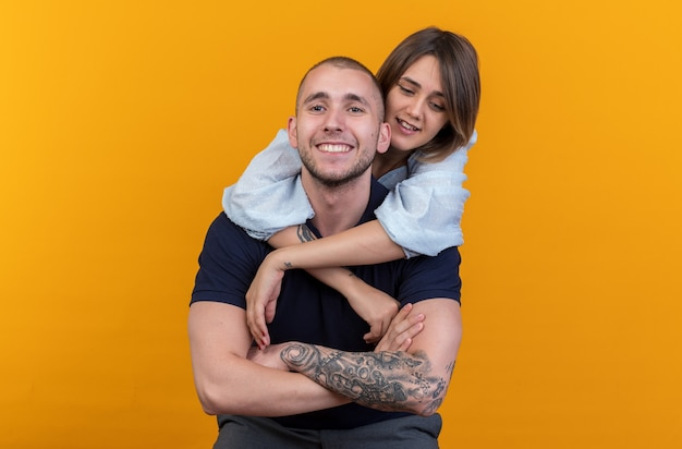 Giovane bella coppia in abiti casual uomo e donna che si abbracciano felici innamorati sorridendo allegramente in piedi