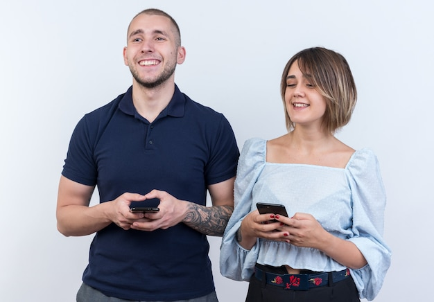 Giovane bella coppia in abiti casual uomo e donna felice e positivo che tiene gli smartphone che guardano da parte con un sorriso sul viso in piedi