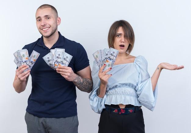 Giovane bella coppia in abiti casual uomo e donna in possesso di contanti che sembrano sorridenti allegramente in piedi