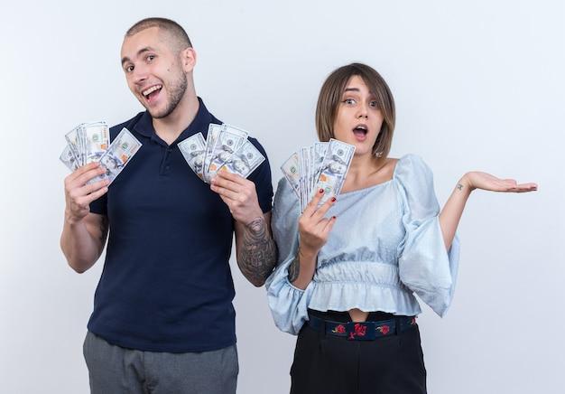 Giovane bella coppia in abiti casual uomo e donna che tengono contanti sorridendo allegramente in piedi sul muro bianco